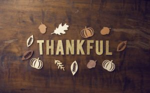 thankful on brown table with leaves